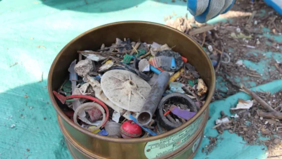 Une corbeille qui montre plusieurs déchets, notamment des gobelets de plastique et des sacs.