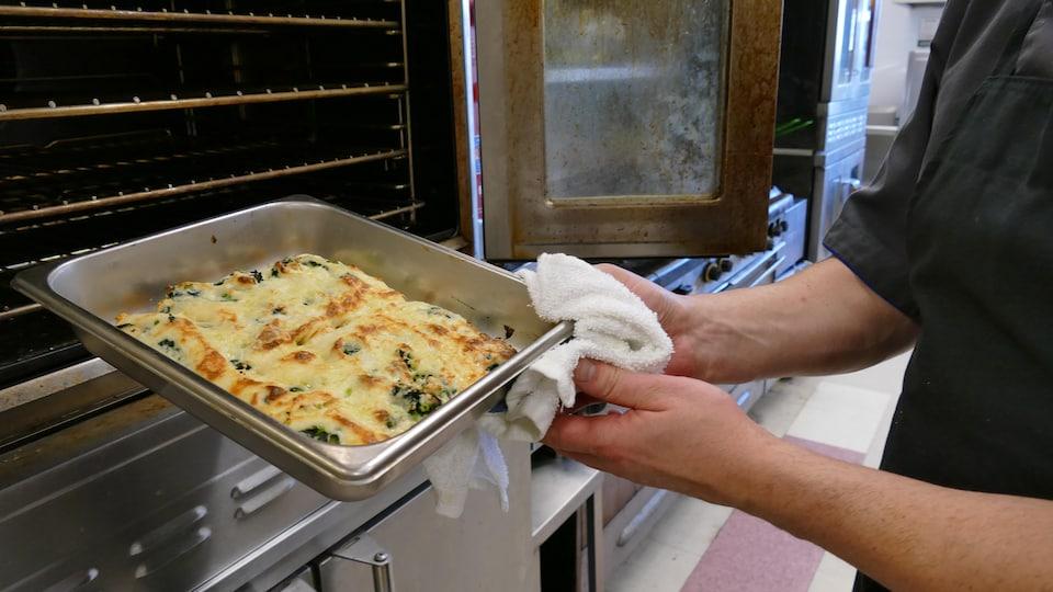 Luc sort le plat de cannellonis du four.