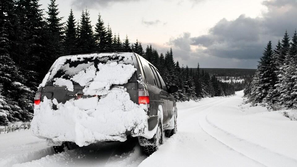 Fourgonnette couverte de neige sur une route rurale enneigée.