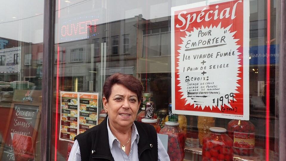 Une femme debout devant la vitrine d'un restaurant dans laquelle on voit des pots de piments et une affiche.