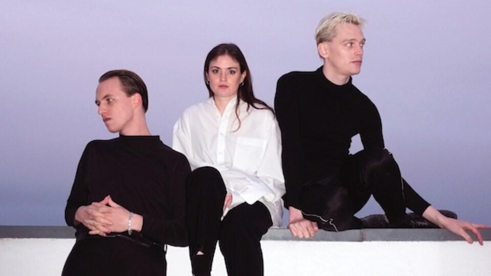 Une jeune femme pose entourée de deux jeunes hommes.