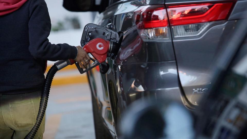 Faire le plein d'essence dans une station-service.