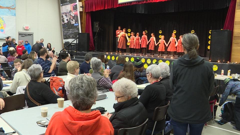 Des danseuses sur scène saluent le public.