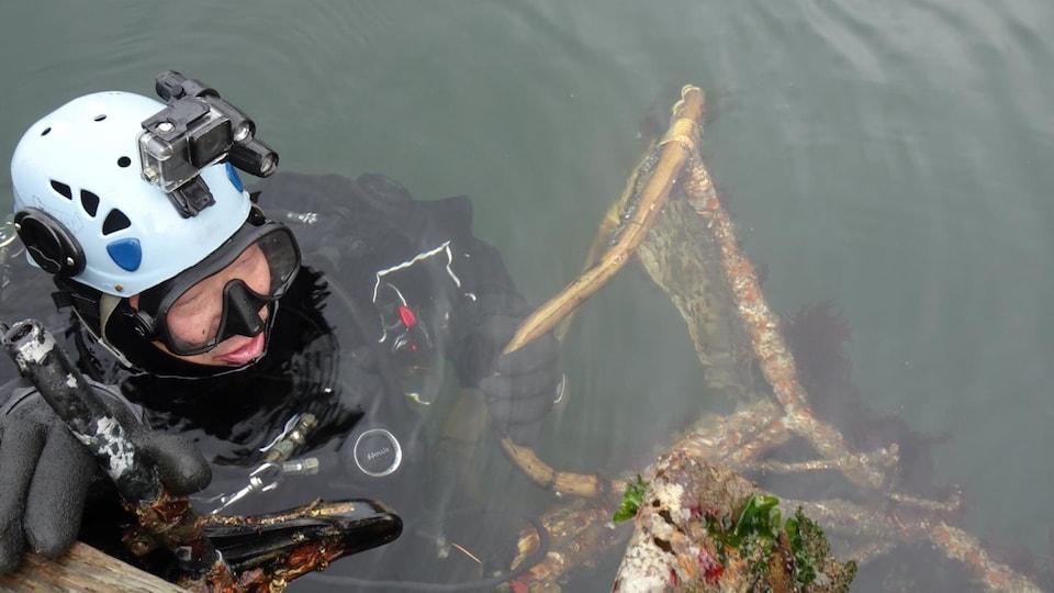 Un plongeur sous-marin tient une chaise à la surface de l'eau.