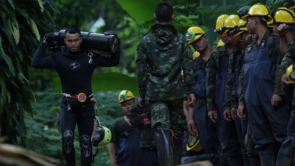 Un plongeur porte une bonbonne d'oxygène en passant devant plusieurs soldats.