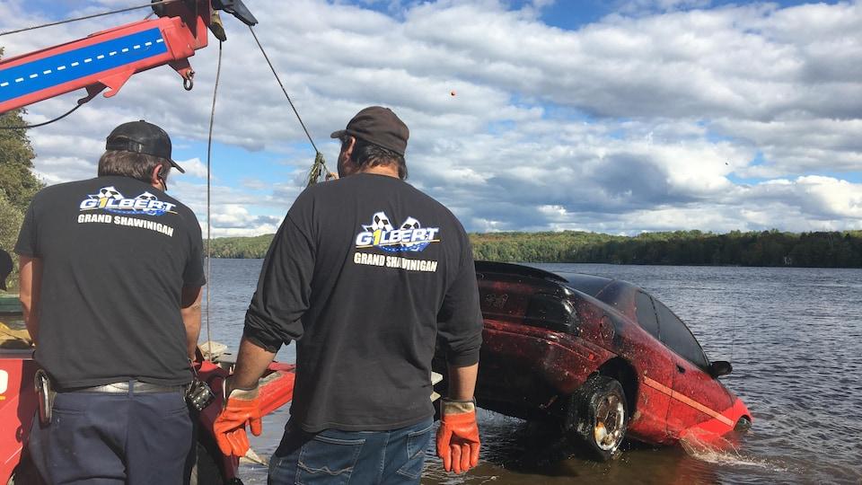Deux opérateurs de dépanneuse remorquent un véhicule. L'automobile est tirée par le crochet de la dépanneuse et sort de la rivière.