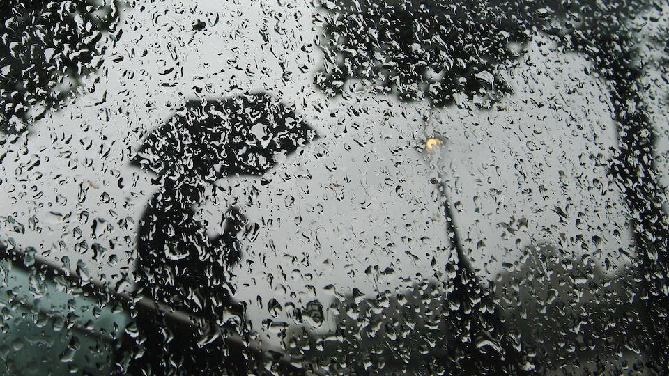 Un homme marche avec un parapluie derrière une vitre pleine de gouttes.