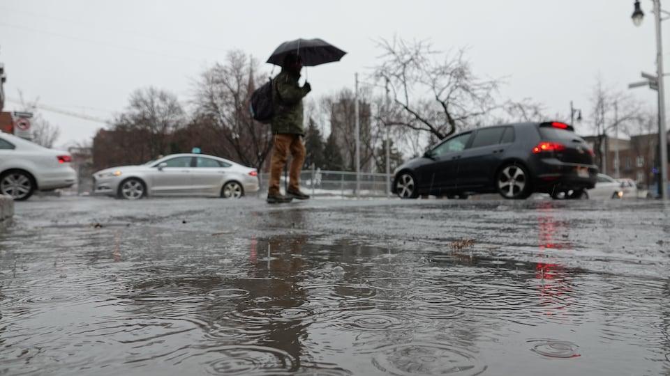 Un homme traverse la rue, inondée d'eau de pluie