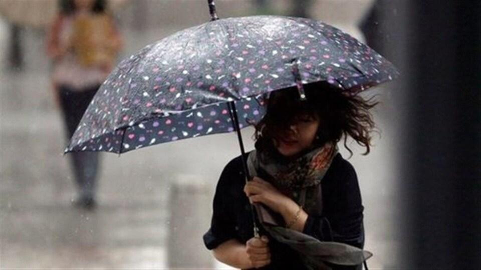 Une femme sous un parapluie.