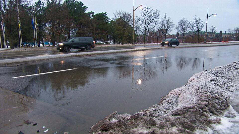 Une flaque d'eau occupe toute une voie d'une rue de Gatineau. Des voitures circulent dans les autres voies.