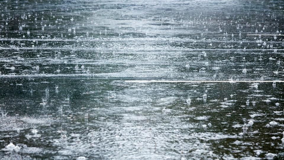 Une photo d'une route inondée par la pluie. De nombreuses gouttes tombent du ciel.