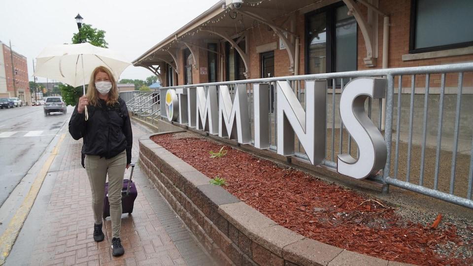 Une femme marche dans une rue de Timmins avec un parapluie. Elle porte un masque.