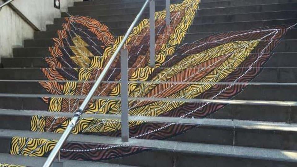 Une plume dessinée dans un escalier.