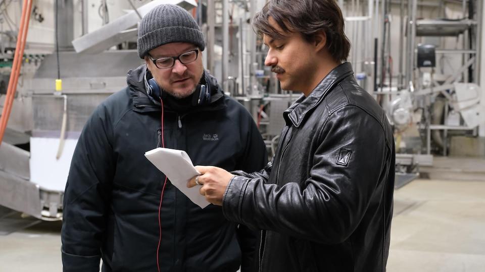 Les deux hommes regardent une feuille de papier.