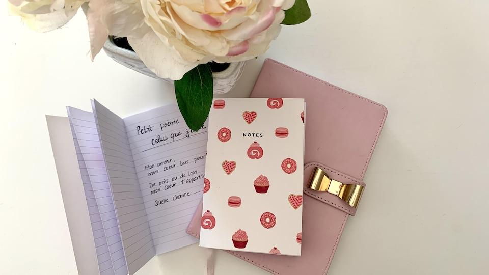 Des carnets de notes placés sur une table, près d'un bouquet de fleurs.