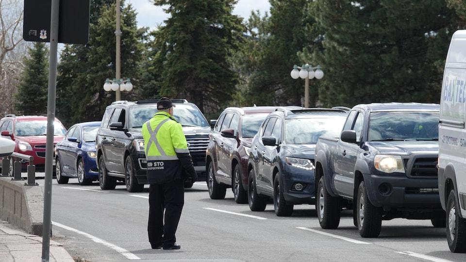 Un agent près d'une file de voitures sur un pont.