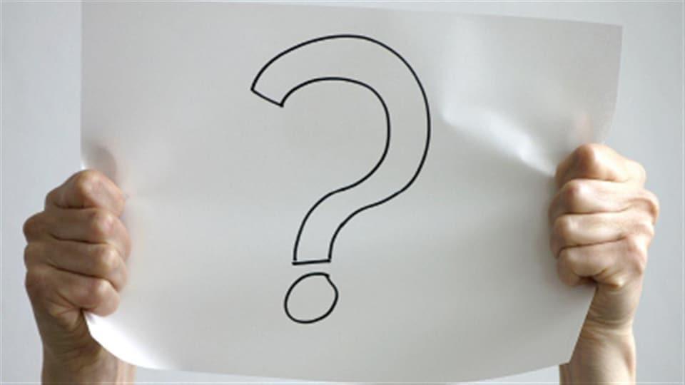 Photo en couleur de mains tenant une feuille sur laquelle est dessiné un point d'interrogation.