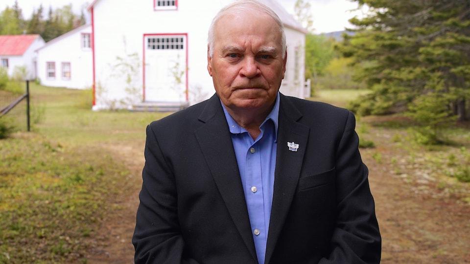 Le maire est debout devant la première chapelle du village.