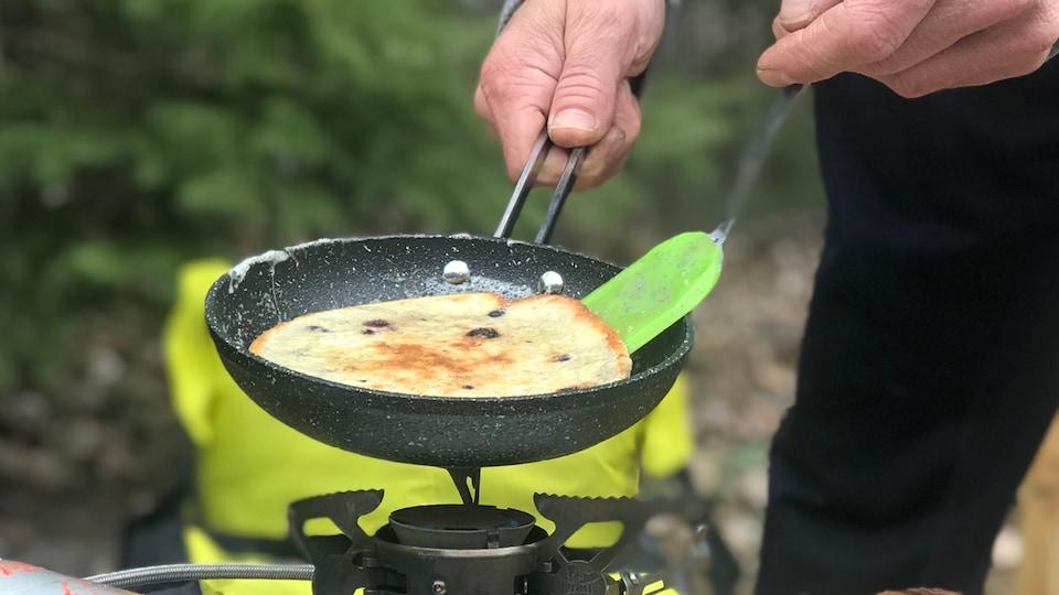 Un homme cuisine des pancakes en camping.