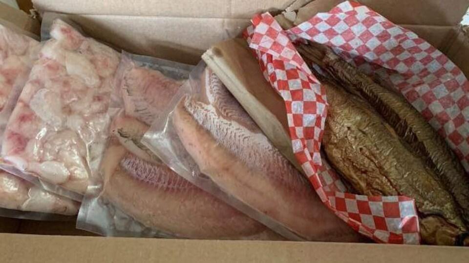 Une boîte remplie de poissons prêts à être livrés.