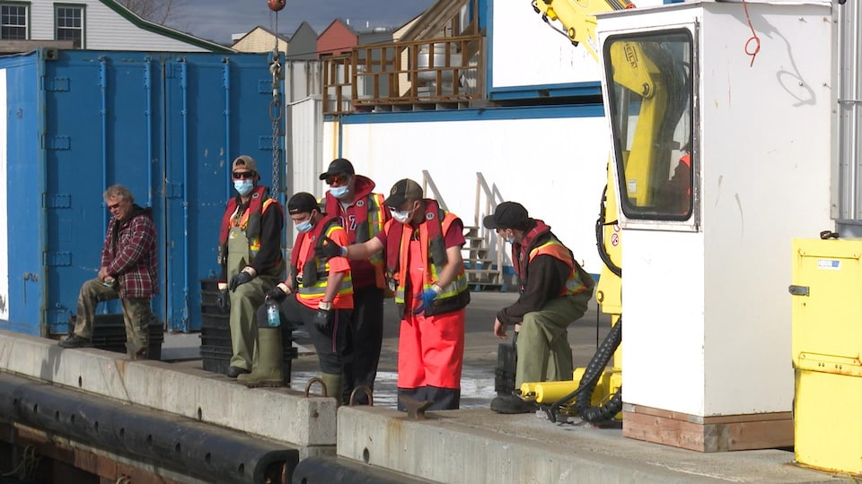Des pêcheurs portent le masque et attendent l'arrivée d'un bateau.