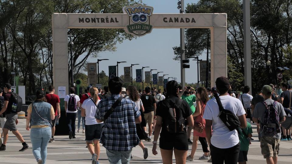 Des dizaines de personnes marchent en direction de l'entrée du site, à travers un portail portant le logo de l'événement Pokémon Go Safari Zone.
