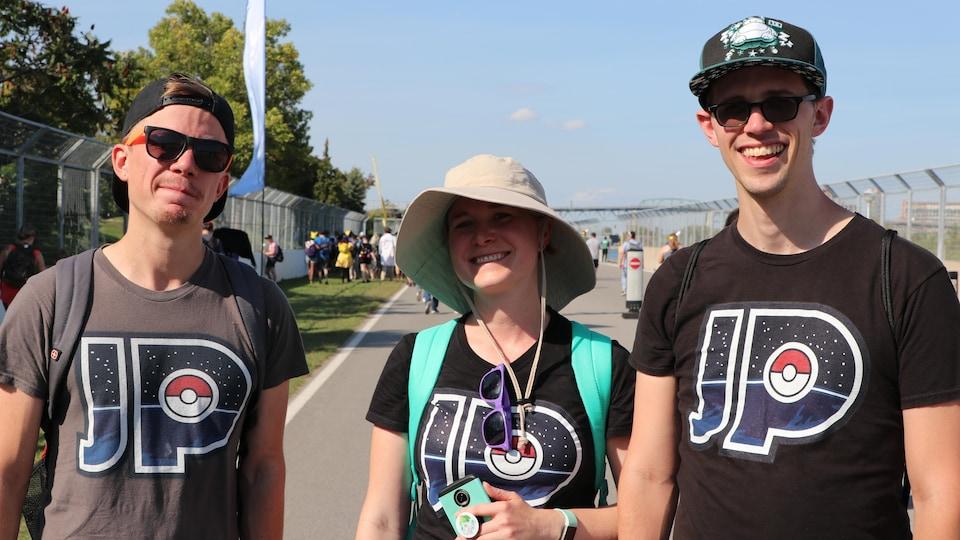 Trois personnes vêtues de t-shirts portant les lettres « J » et « P ».