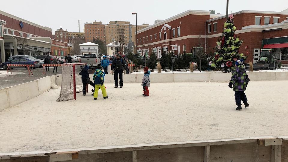 Des enfants jouent au hockey sur une glace extérieure.
