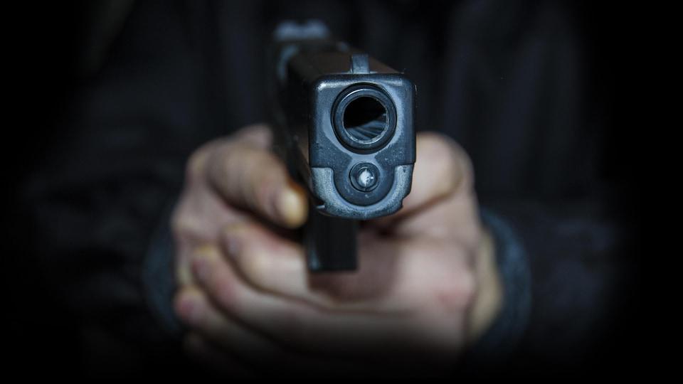 Une main tient un revolver.