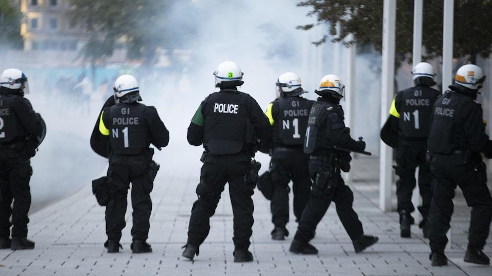 Un rang de policiers monte la garde dans les fumées de gaz lacrymogène.