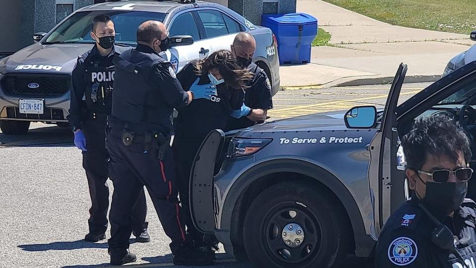 Des policiers maîtrisent un homme.
