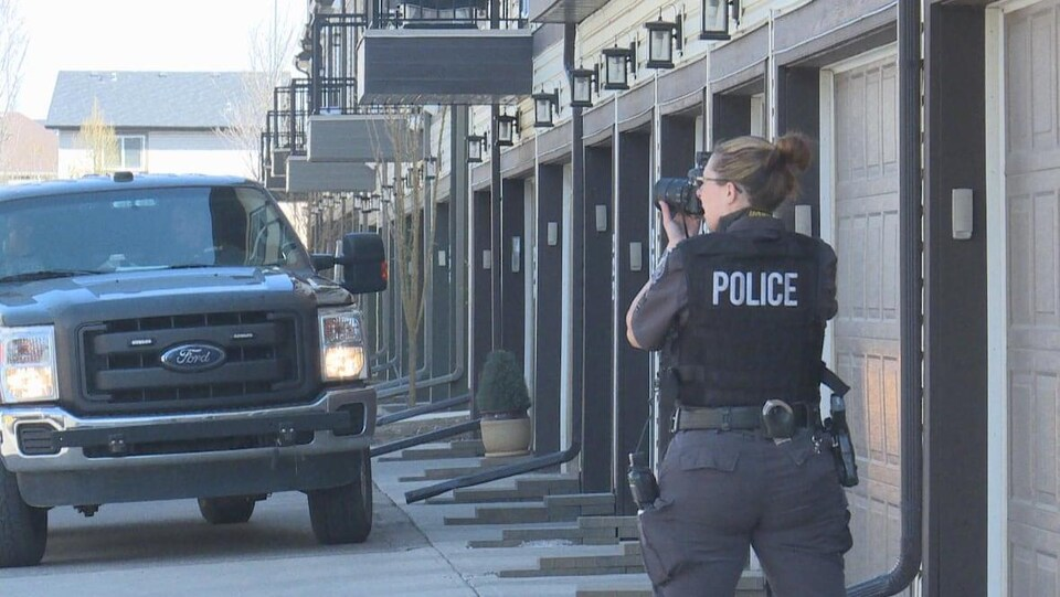 Un officier de police prend des photos dans un complexe de maisons devant des garages