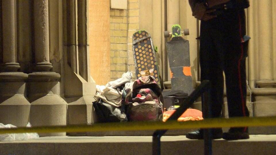 Des affaires, des sacs à dos et des planches à roulettes sur le perron d'une église avec les jambes d'un policier, qui est posté devant, la nuit.