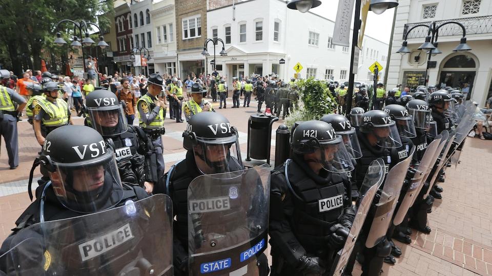 Des policiers de l'État de la Virginie, munis de visières et de boucliers, forment un cordon humain autour du lieu où un véhicule a foncé dans la foule