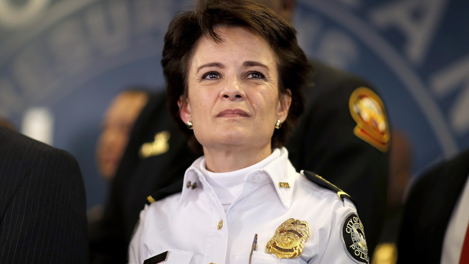 Une femme aux cheveux bruns et courts, portant l'uniforme de la police, regarde au loin.