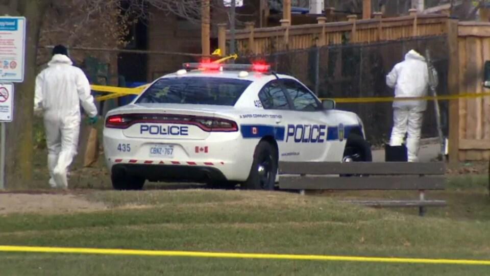 Deux enquêteurs près d'une voiture de police.