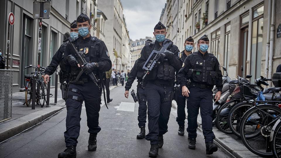 Des agents de police armés de fusils automatiques marchent dans la rue.