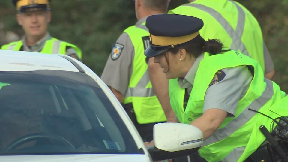 Une policière parle à un conducteur assis dans sa voiture.