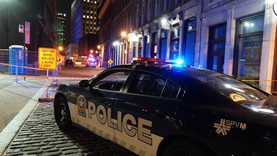 Une voiture de police est garée devant un périmètre de sécurité.