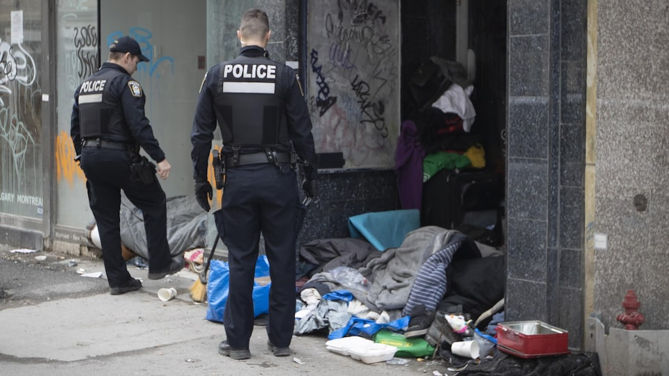 Des policiers près d'une entrée de logement devant lequel on voit plein de détritus et de vêtements qui jonchent le sol.