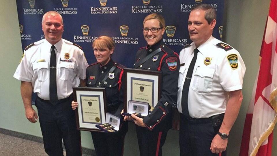 Les quatre policiers sont debout côte-à-côte et souriant
