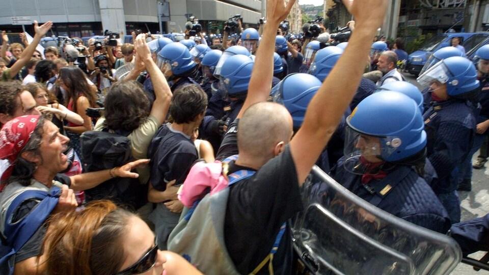 Des manifestants sont repoussés par une ligne de policiers anti-émeute dans une rue de Gênes, en Italie.