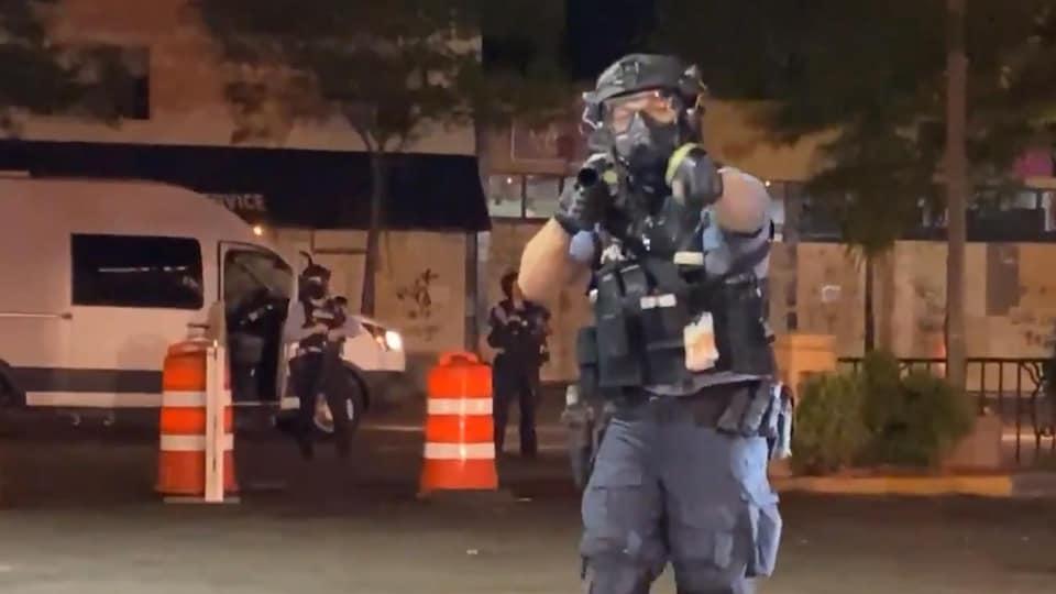 Un policier visant son arme en direction du journaliste.