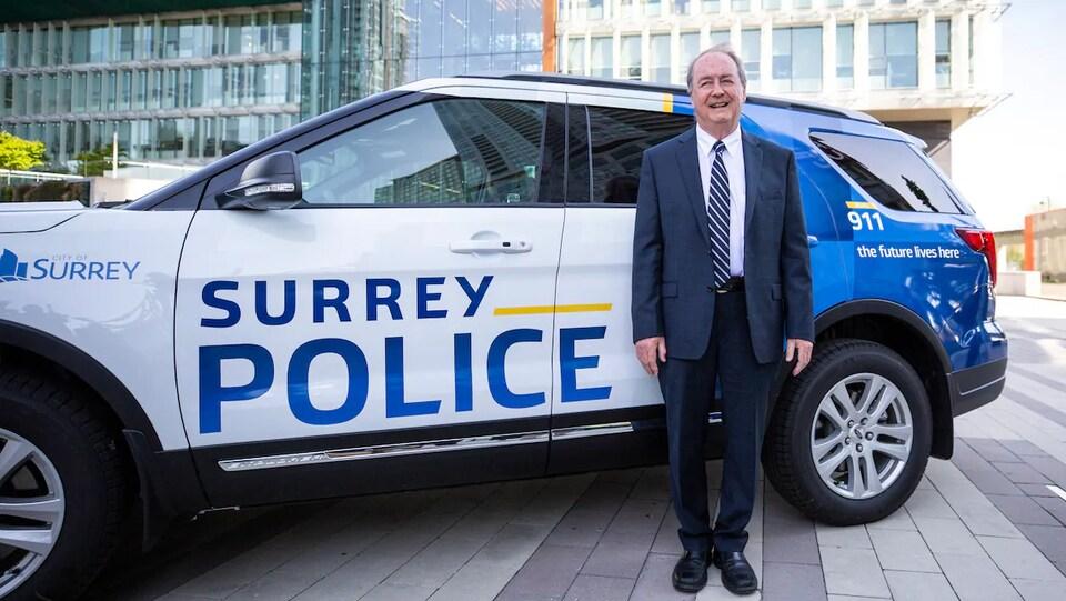 """Un véhicule de police bleu, blanc et jaune avec les mots """"Surrey Police"""" inscrits sur la porte en lettres capitales était stationné devant l'hôtel où M. McCallum a parlé."""