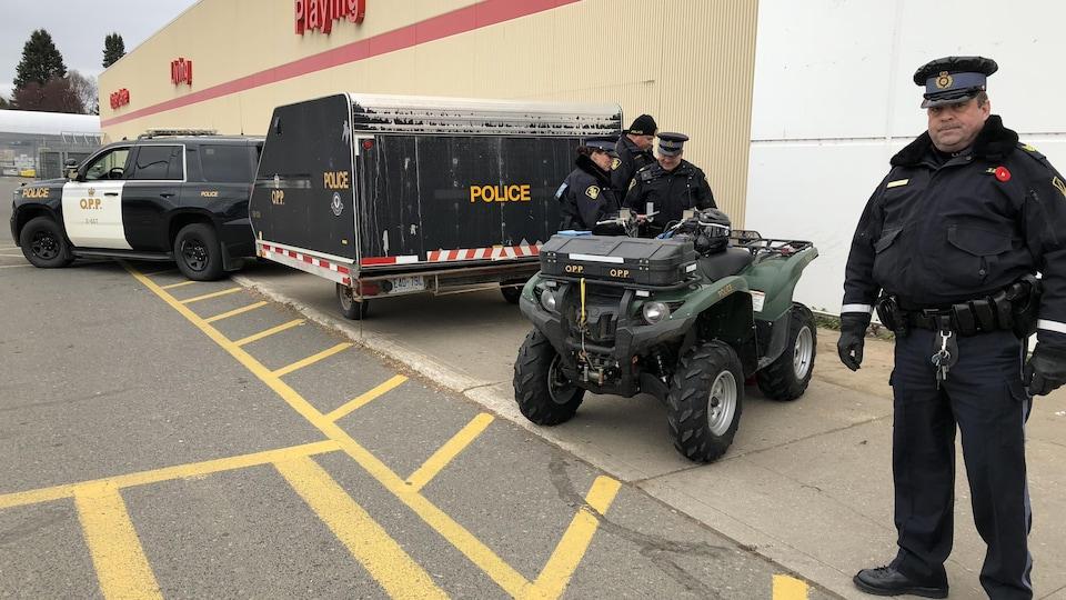 Des policiers entourant un véhicule tout-terrain dans un stationnement.