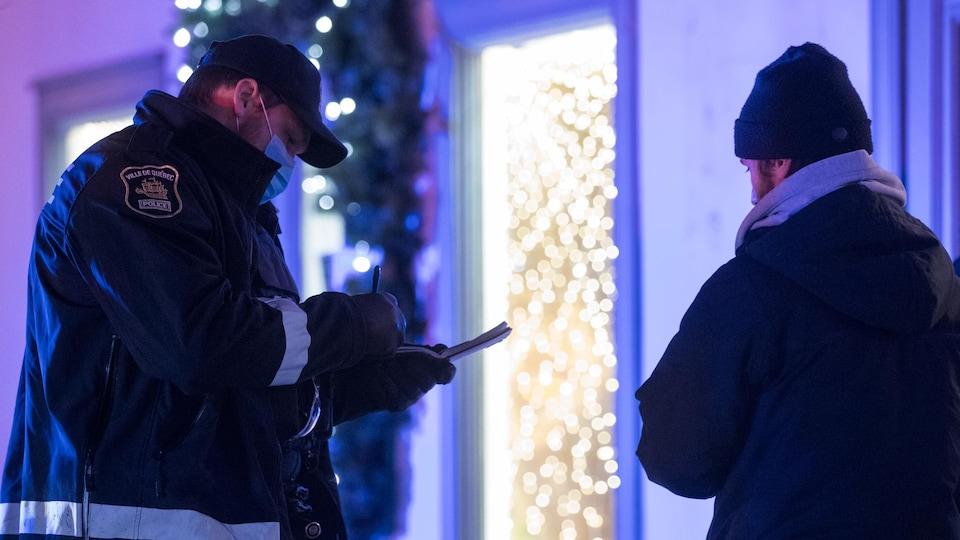 Un policier de la Ville de Québec remet un constat d'infraction.
