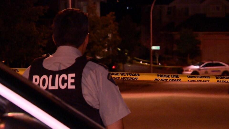 Un agent de police se trouve devant un ruban jaune délimitant la scène d'un crime à Surrey en Colombie-Britannique
