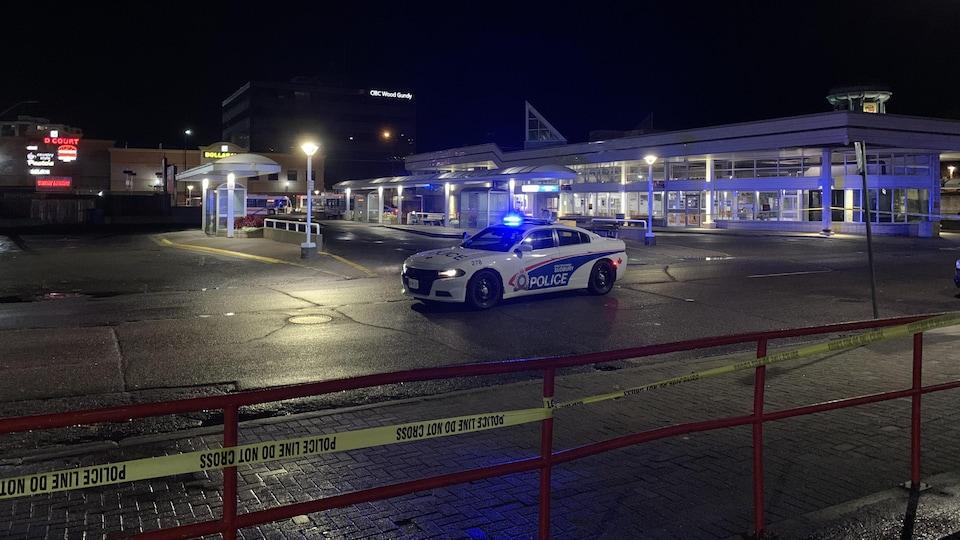 Une voiture de police devant un terminus d'autobus.