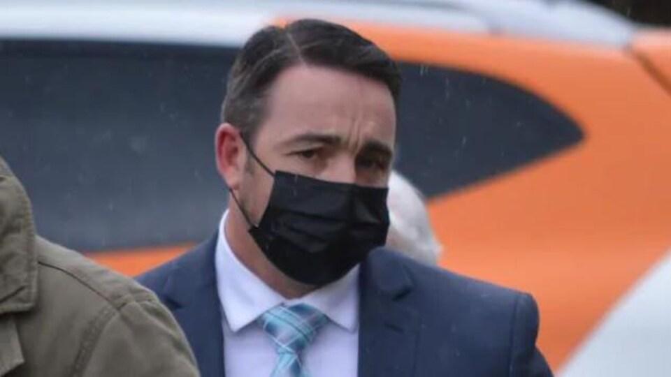 Un homme masqué, au front plissé, marche sous la pluie.