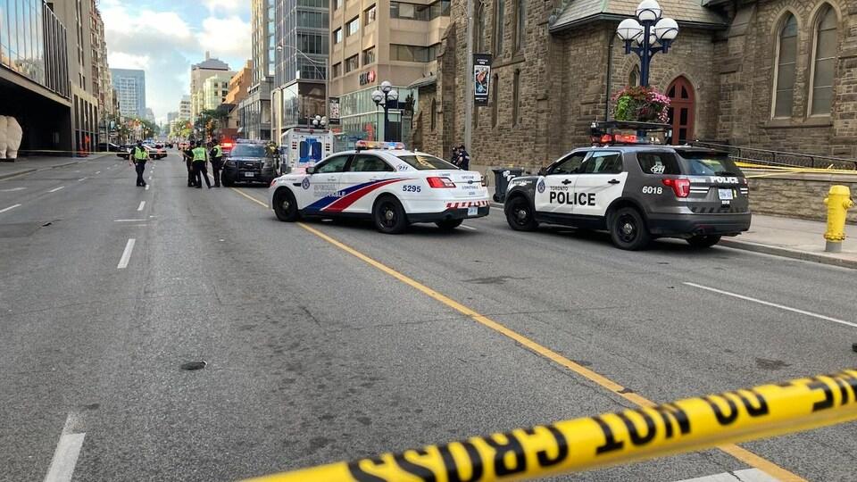 Des véhicules de la police de Toronto bloquent une rue du centre-ville.